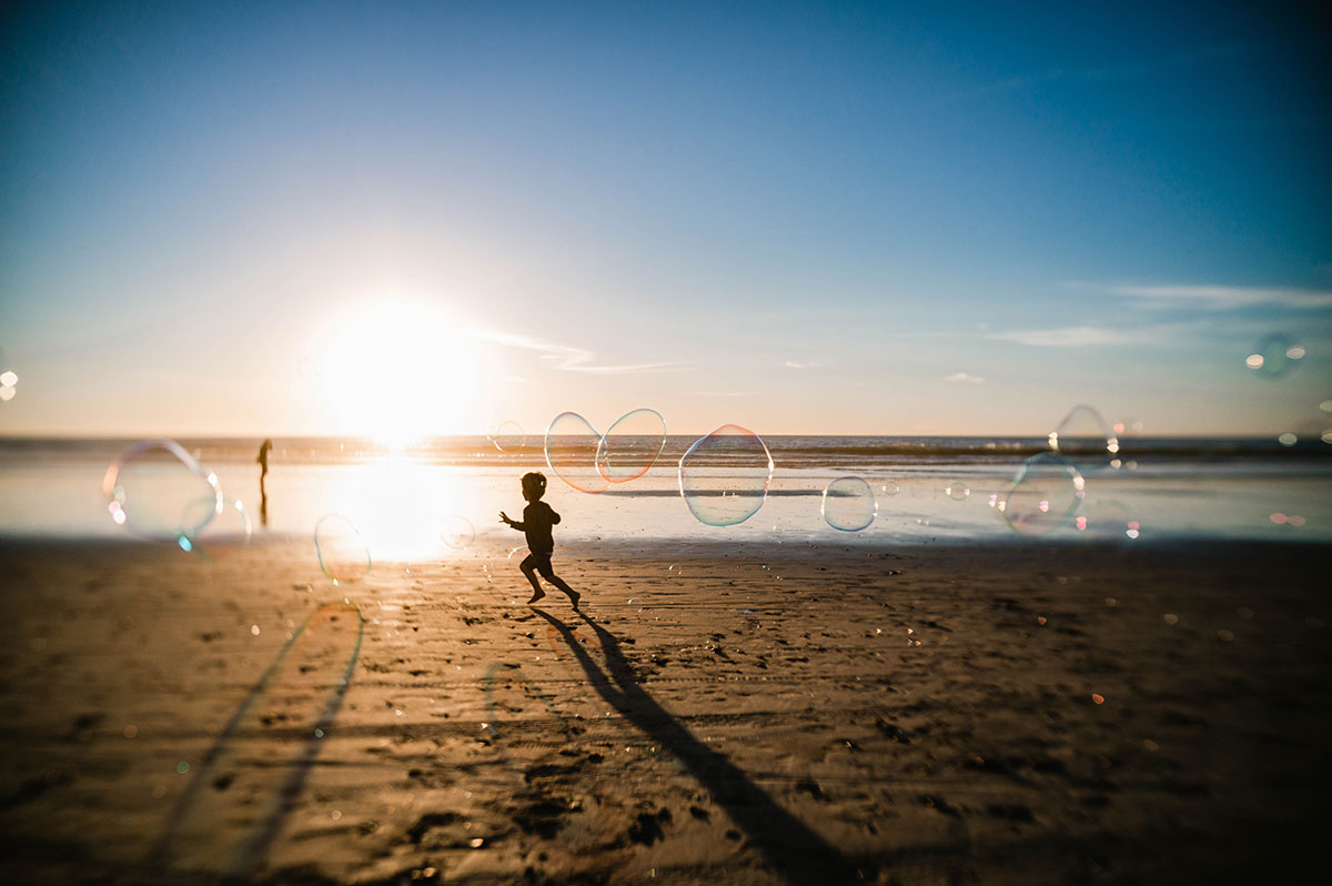 A silhouette of a little boy running down the beach at sunset chasing bubbles.