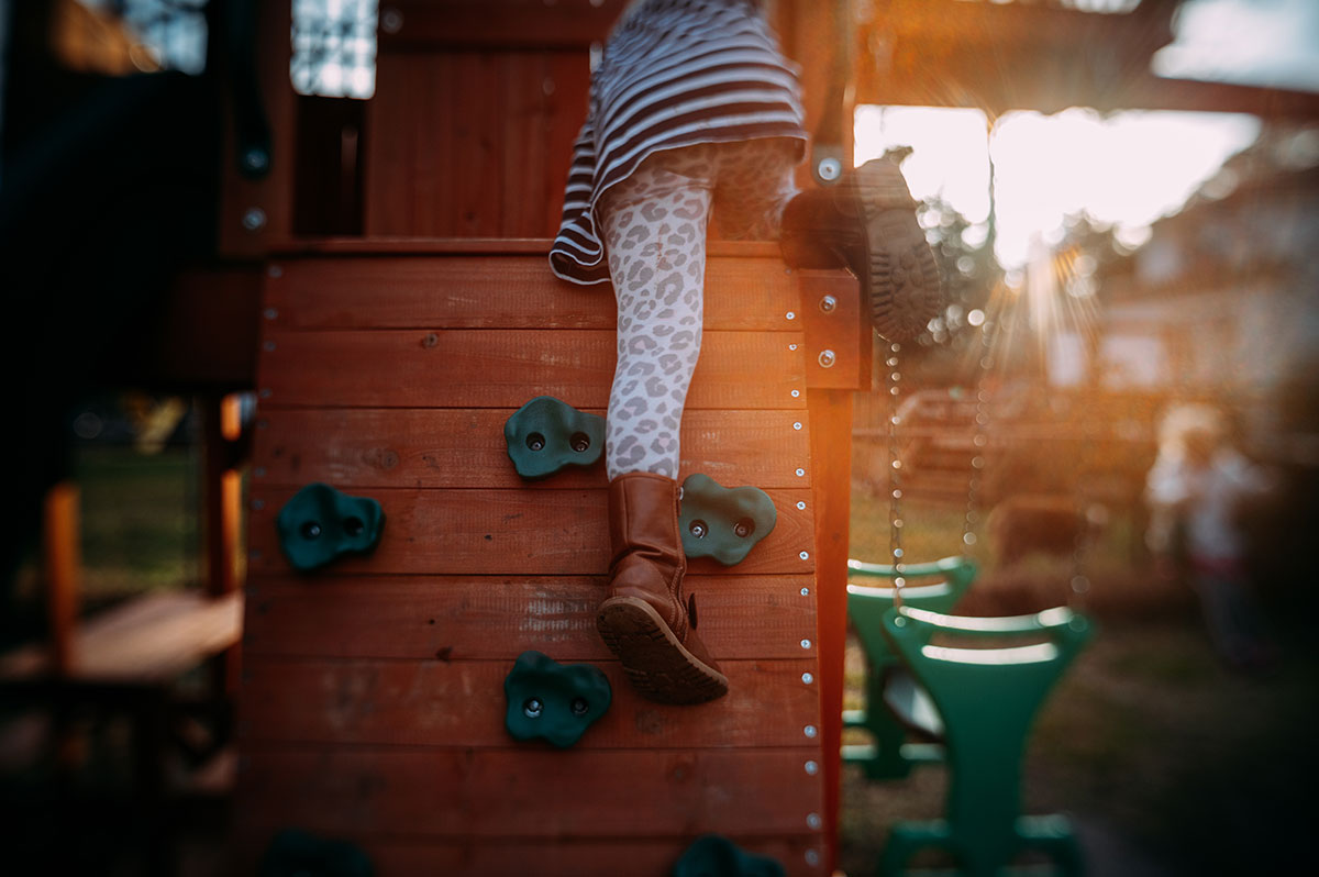 a little girl wearing leopard print pants and stripped shirt crawls up rock wall on playset