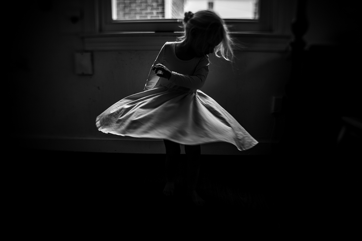 black and white photo of a girl twirling in a dress