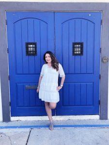 woman standing at blue door