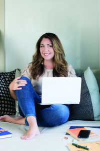 female entrepreneur with laptop writing in the morning