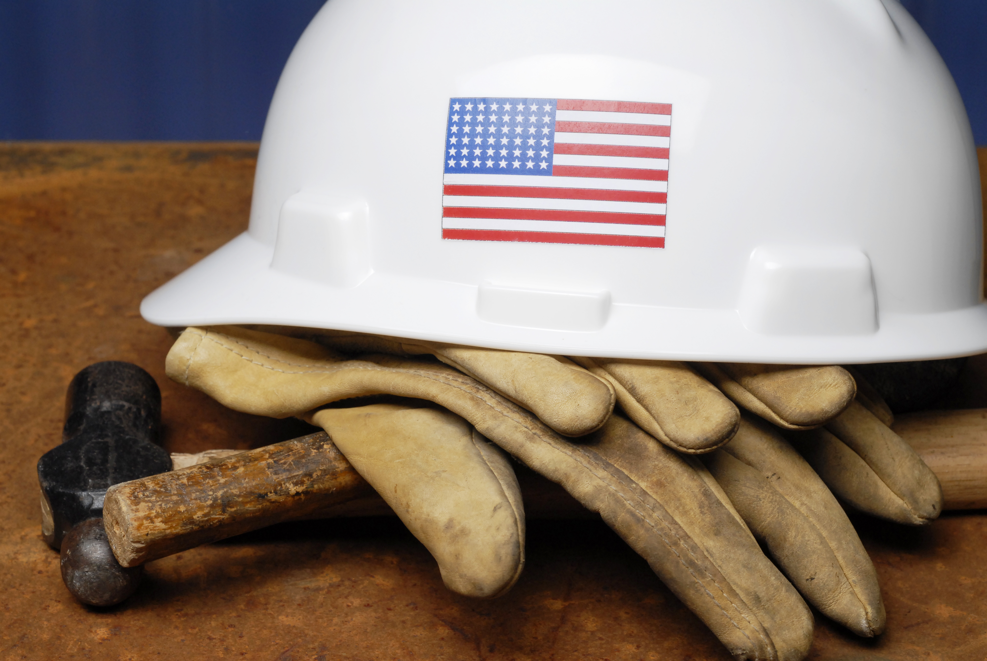Stock Photograph of hard hat with U.S. flag and gloves.