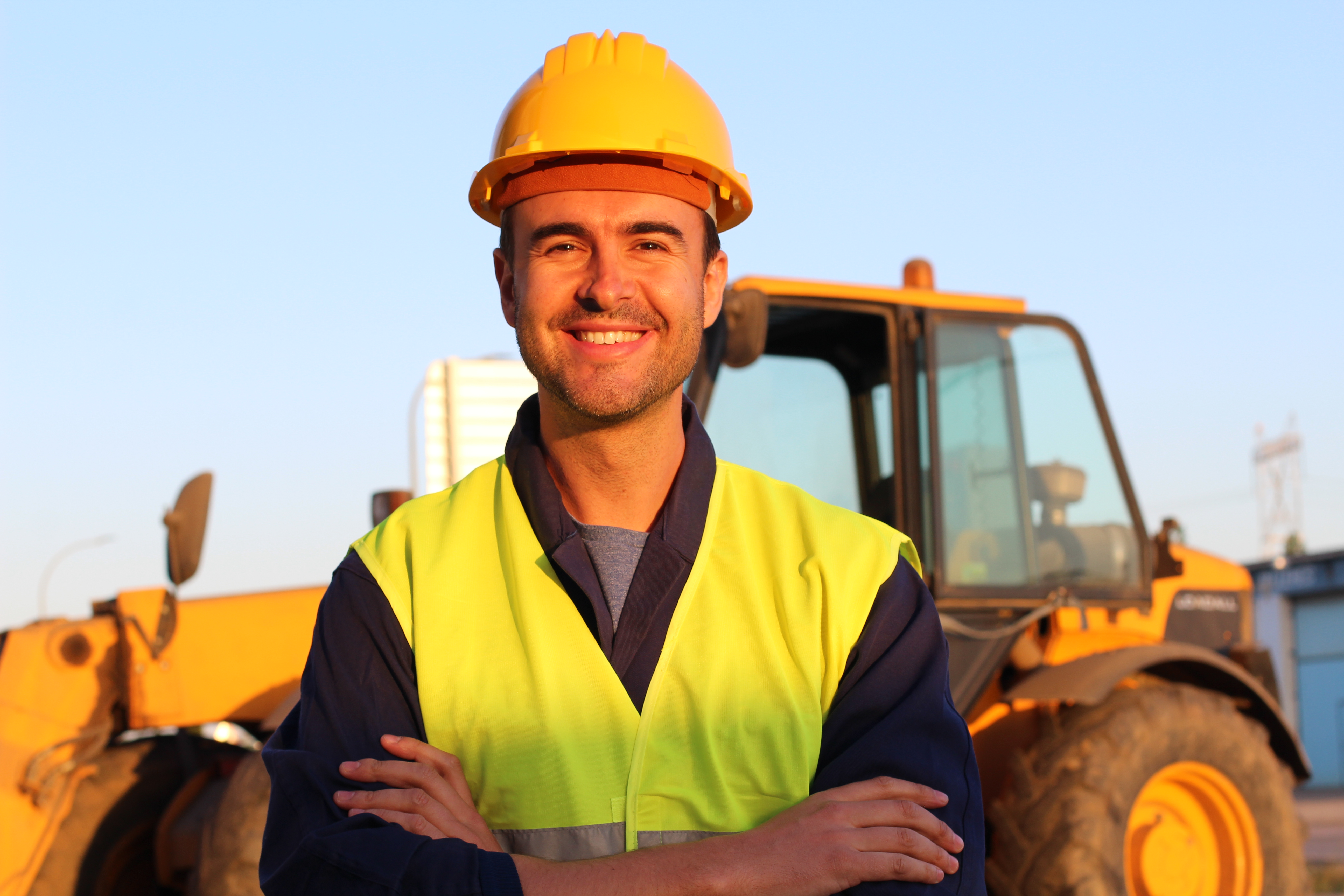 Construction driver with excavator on the background.