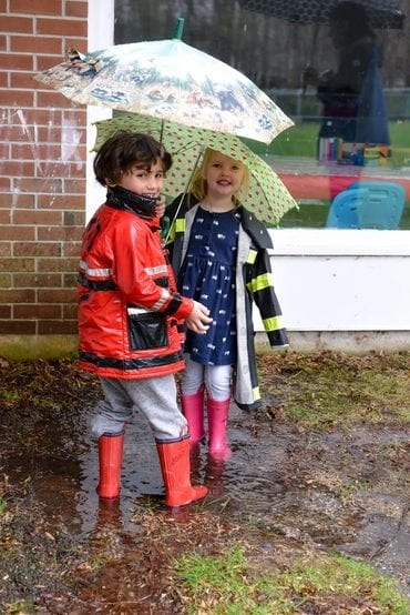 A pair of kids playing in the rain