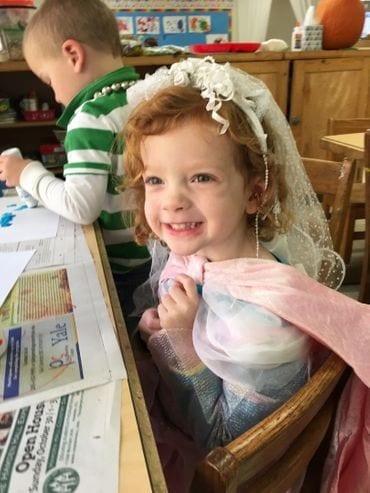 A preschool girl wearing a gown