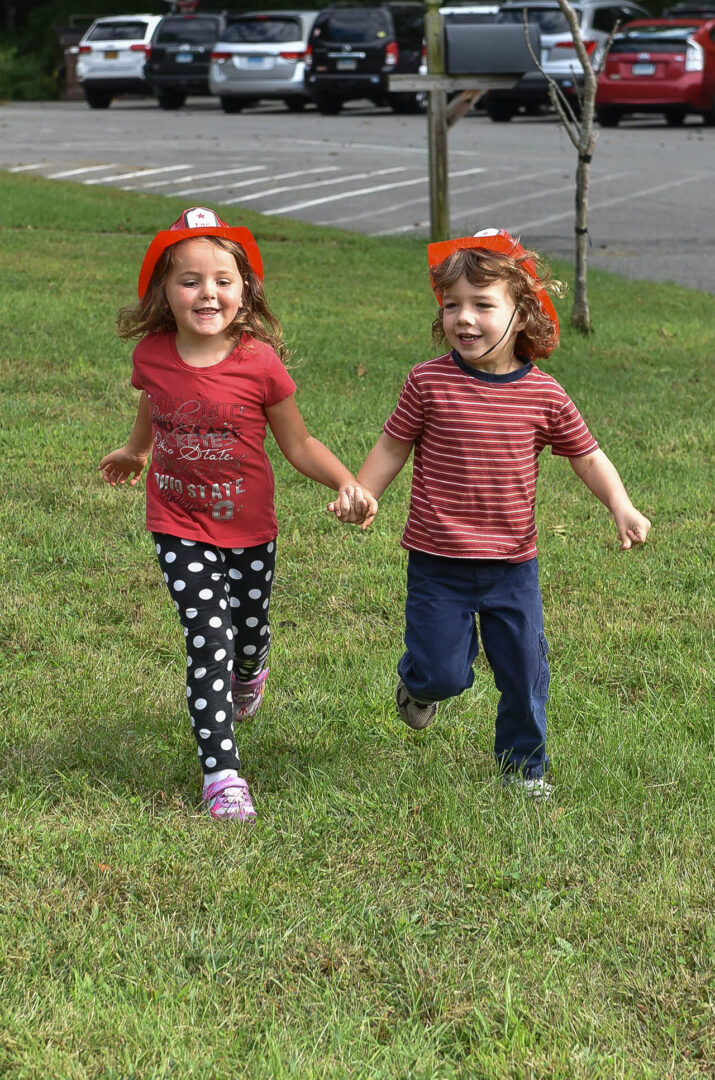 A pair of kids holding hands while running, wearing fireman hats