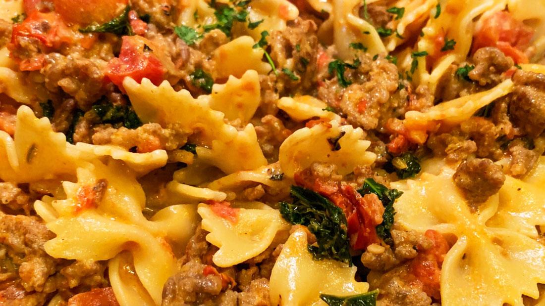 closeup photo of creamy kale and sausage pasta