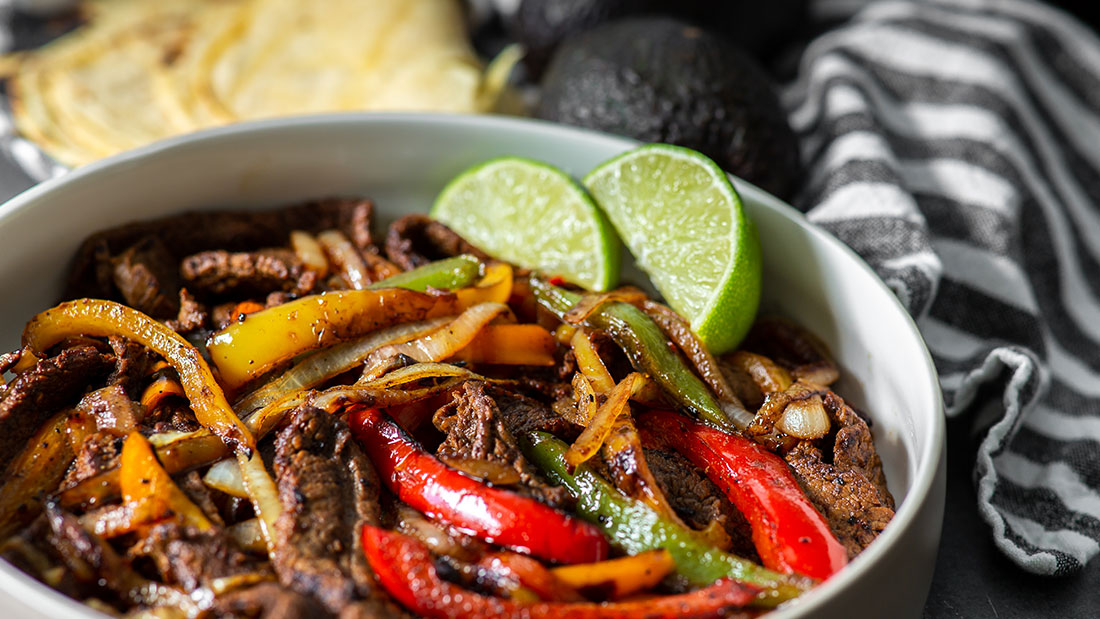 close up of chili lime steak fajitas with tortillas and avocados and lime