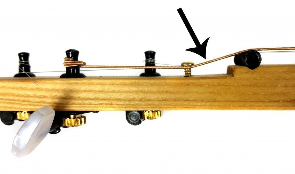 """This photo shows how retaining screws can be used to adjust the """"break angle"""" of the strings - the angle at which they cross over the nut/zero fret. While this photo shows an unfretted cigar box guitar that uses a threaded rod nut, the same concept applies to a guitar using a zero fret."""