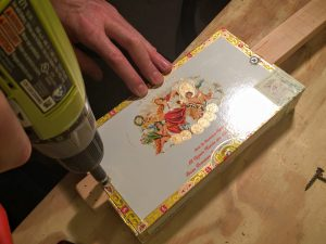 fasten the cigar box lid to the neck