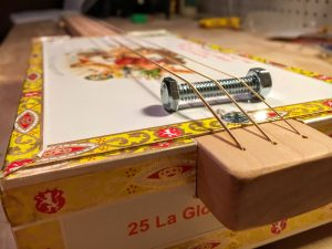 place the bolt bridge on the cigar box lid