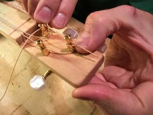 wind the strings around the tuning pegs