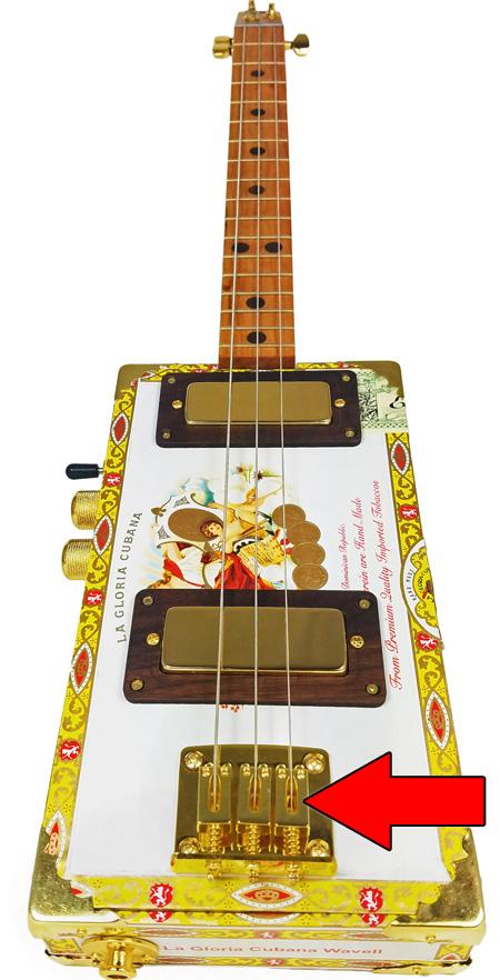 "This cigar box guitar sports a gold-plated 3-string hard-tail bridge. It is a ""Metamorphosis"" model built by Glenn Watt at C. B. Gitty."