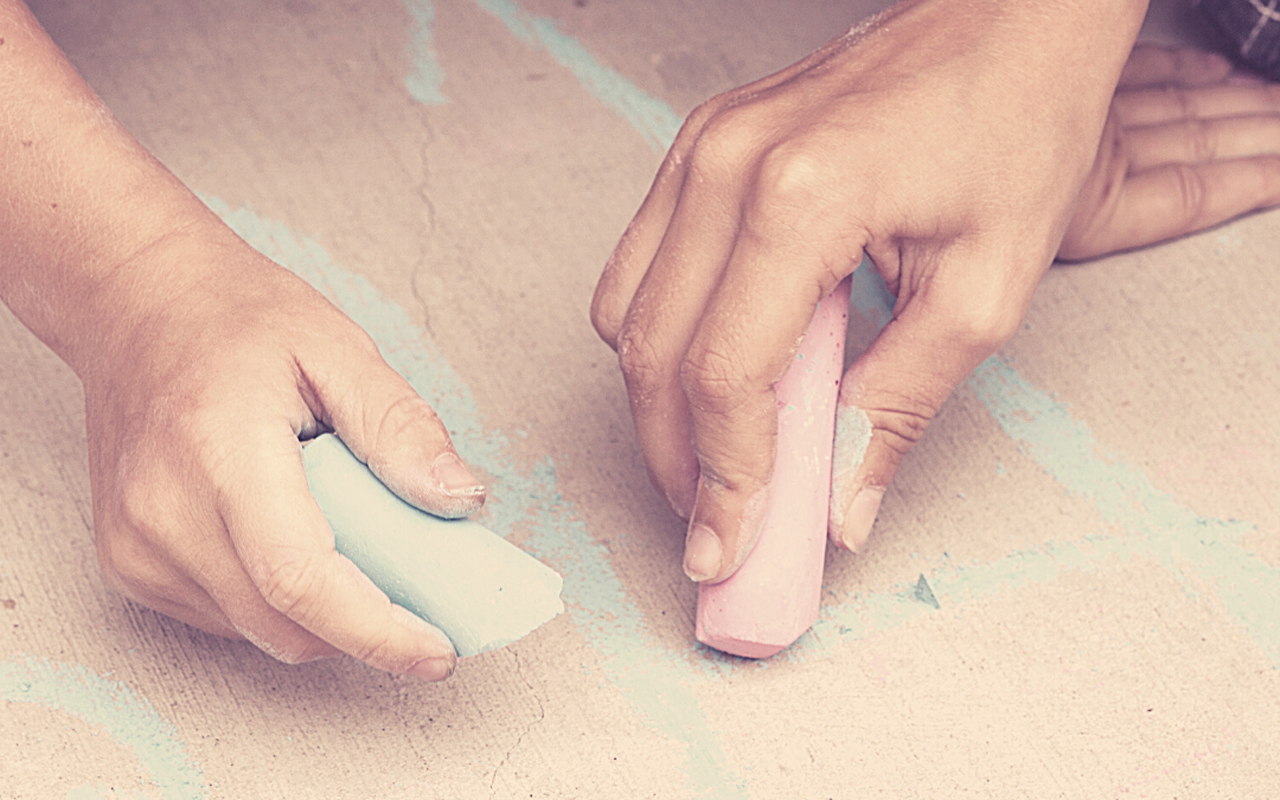 Close up image of hand using chalk to draw on a sidewalk.