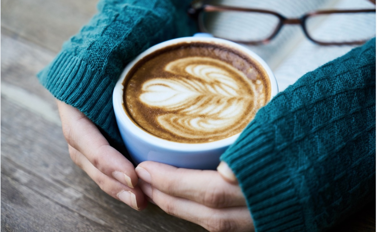 A close up of hand wrapped around a white mug filled with coffee