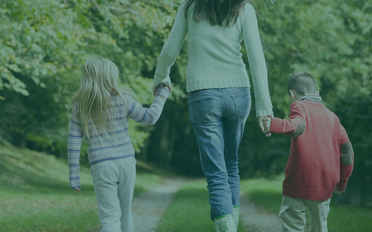 Women holding hands with 2 children and walking down a path