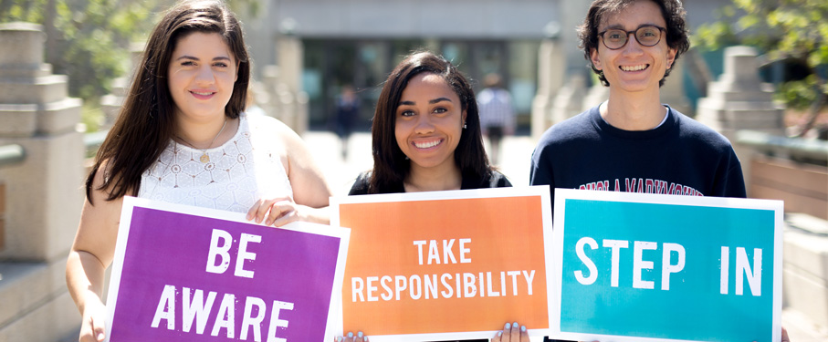 three young people holding inspirational signs and smiling