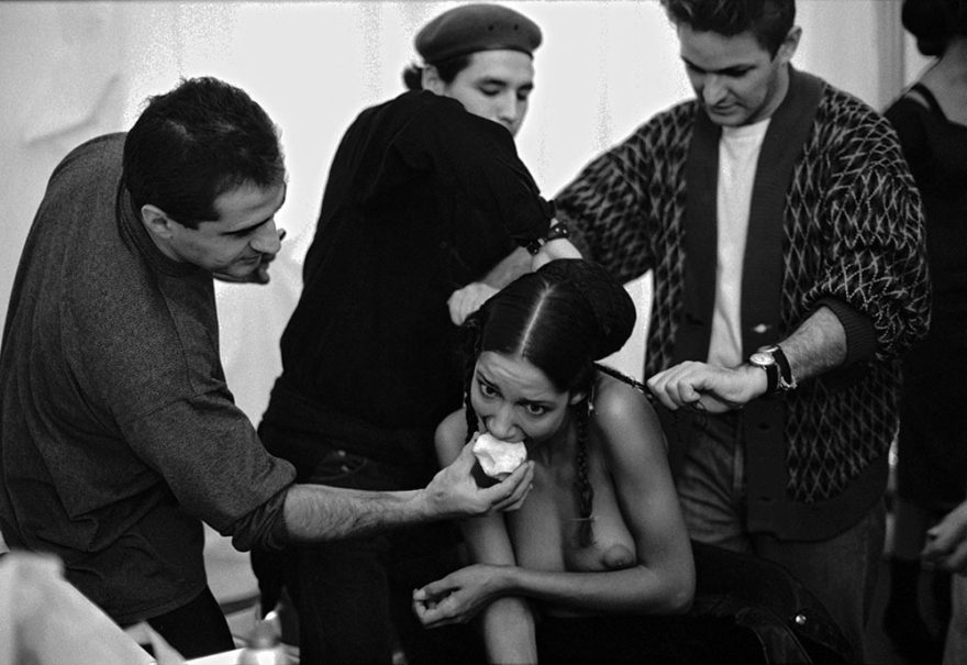 Image of topless model backstage getting fed an apple while her hair is being done for a fashion show. Image by Ferdinando Scianna © Magnum Photos