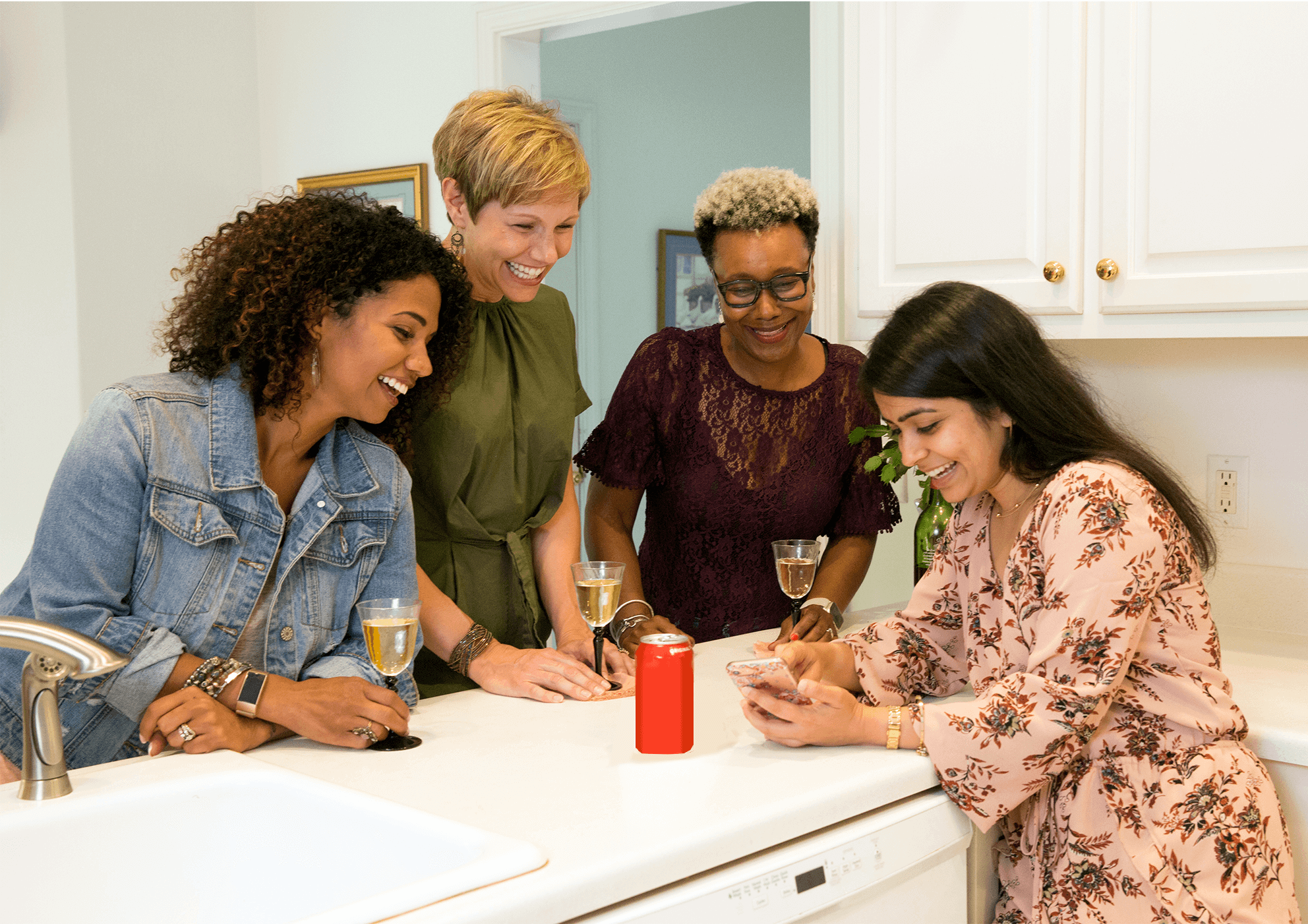 women gathered in kitchen looking at smart phone