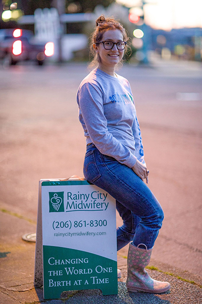 Midwife Sara Alvarado sits on the Rainy City sign after a birth at Center for Birth