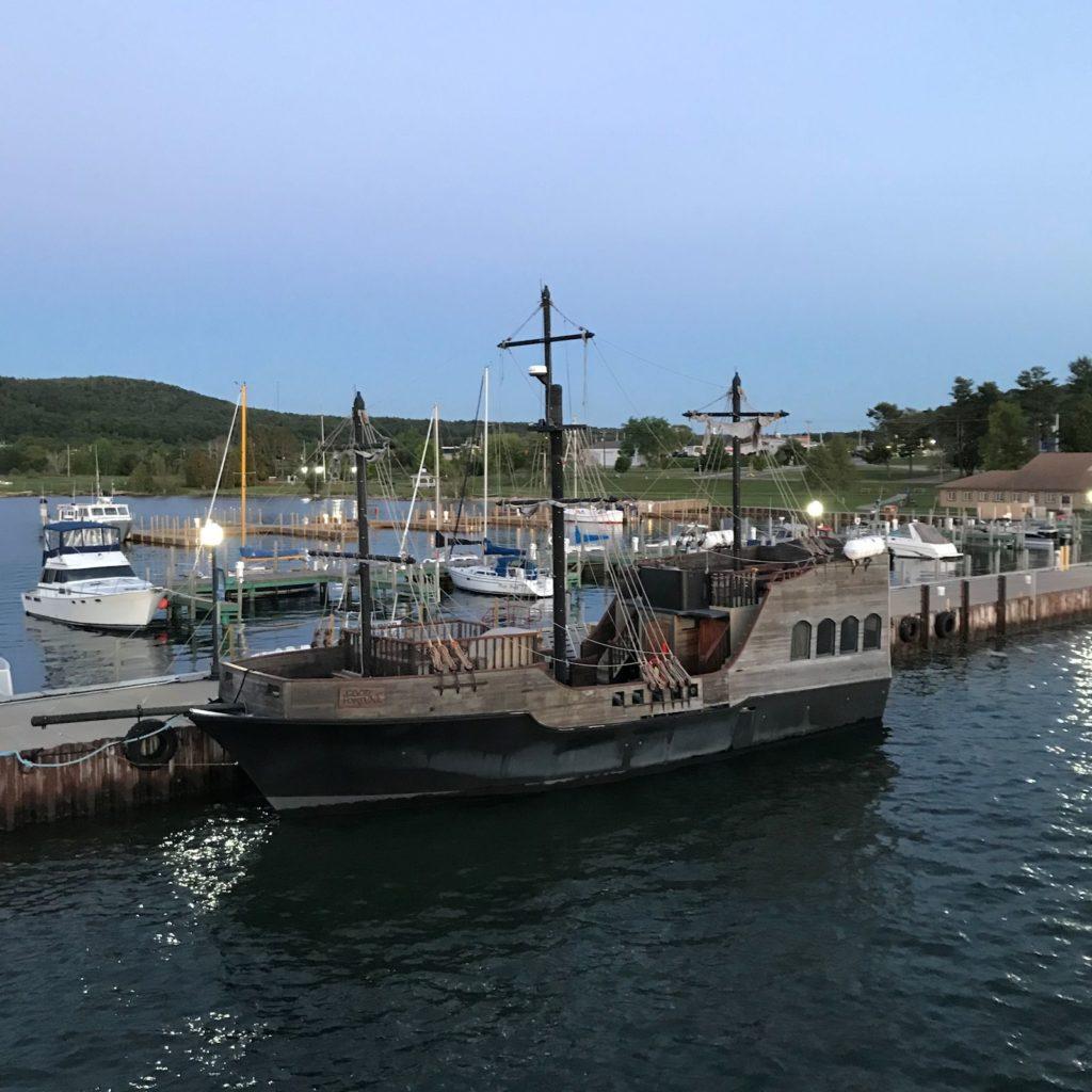 """photo of fake """"pirate ship"""" in Munising Harbor at dusk."""