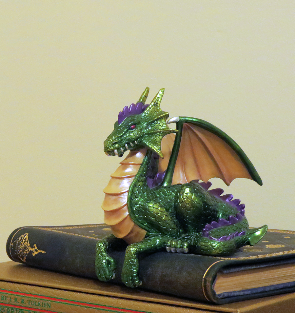 Green dragon shelf-sitter atop a pile of leatherbound books