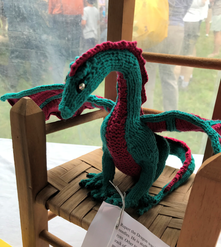 knitted dragon in burgundy and dark green, sitting on miniature woven-seat wooden chair