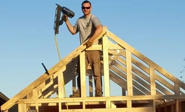man on a roof with a nail gun