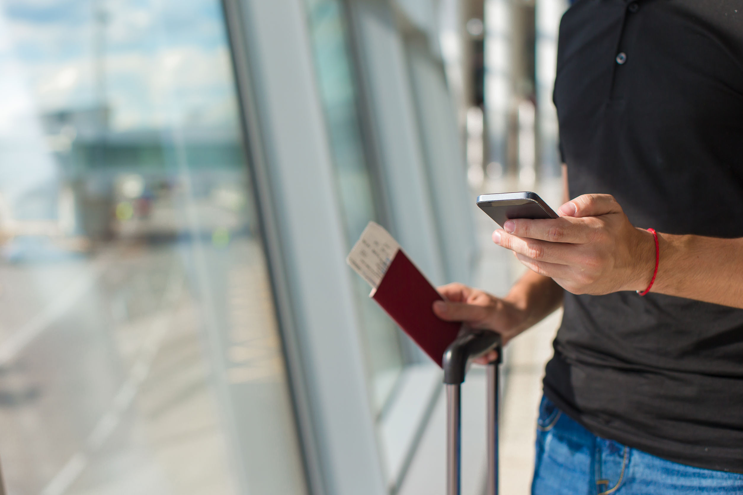 Man holding cell phone, passports and boarding passport at airport waiting the flight