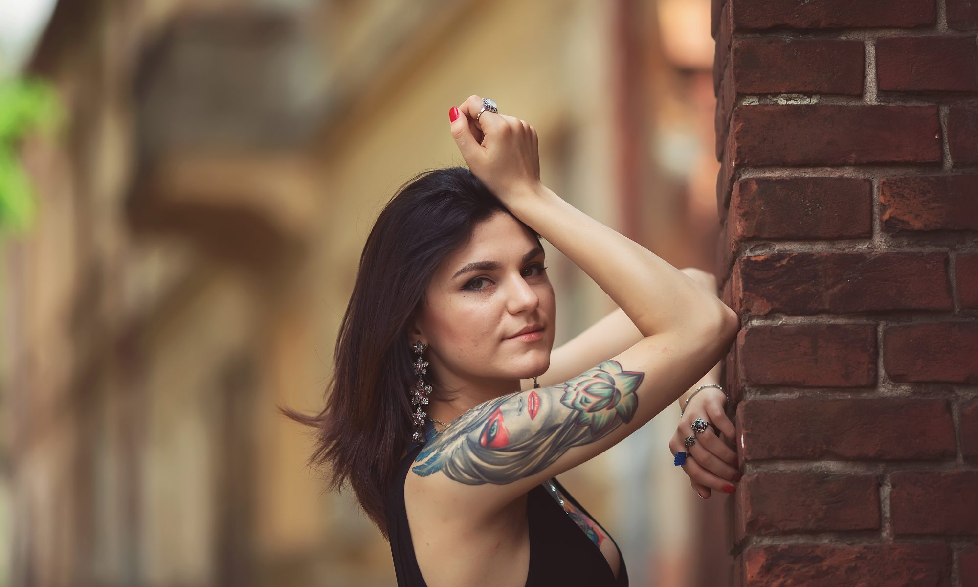 beautiful girl in a black dress stands near architectural struct