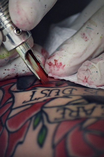 Someone drawing a tattoo