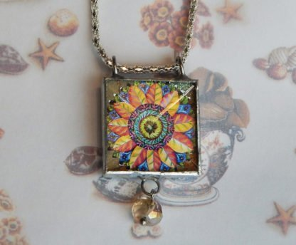 Danasimson.com Looking glass double-sided glass pendent pop-art flower. Beveled glass with a bead detail.