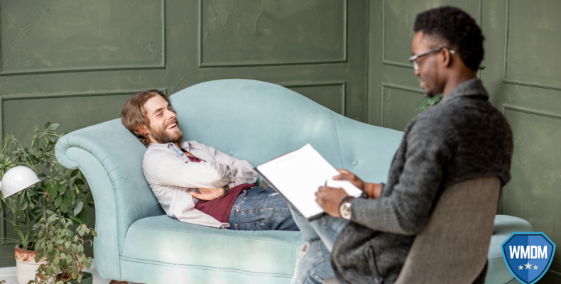 Psychologist on a chair with a patient resting on a blue couch.