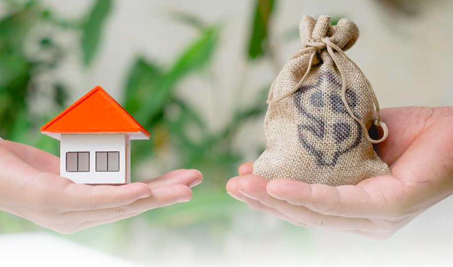 a hand holding a tiny house and another hand holding a bag of money