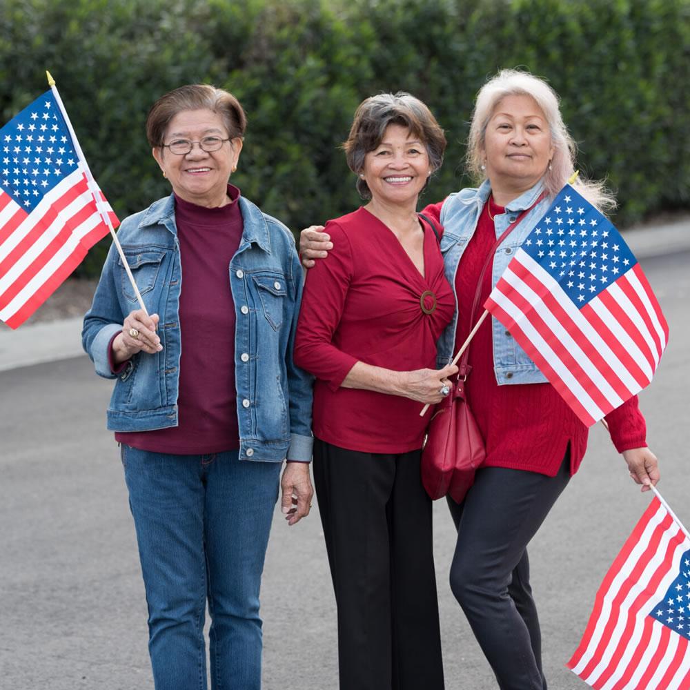 Three smiling senior women each holding an American flag.