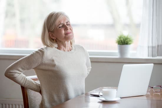 woman experiencing pain at a desk