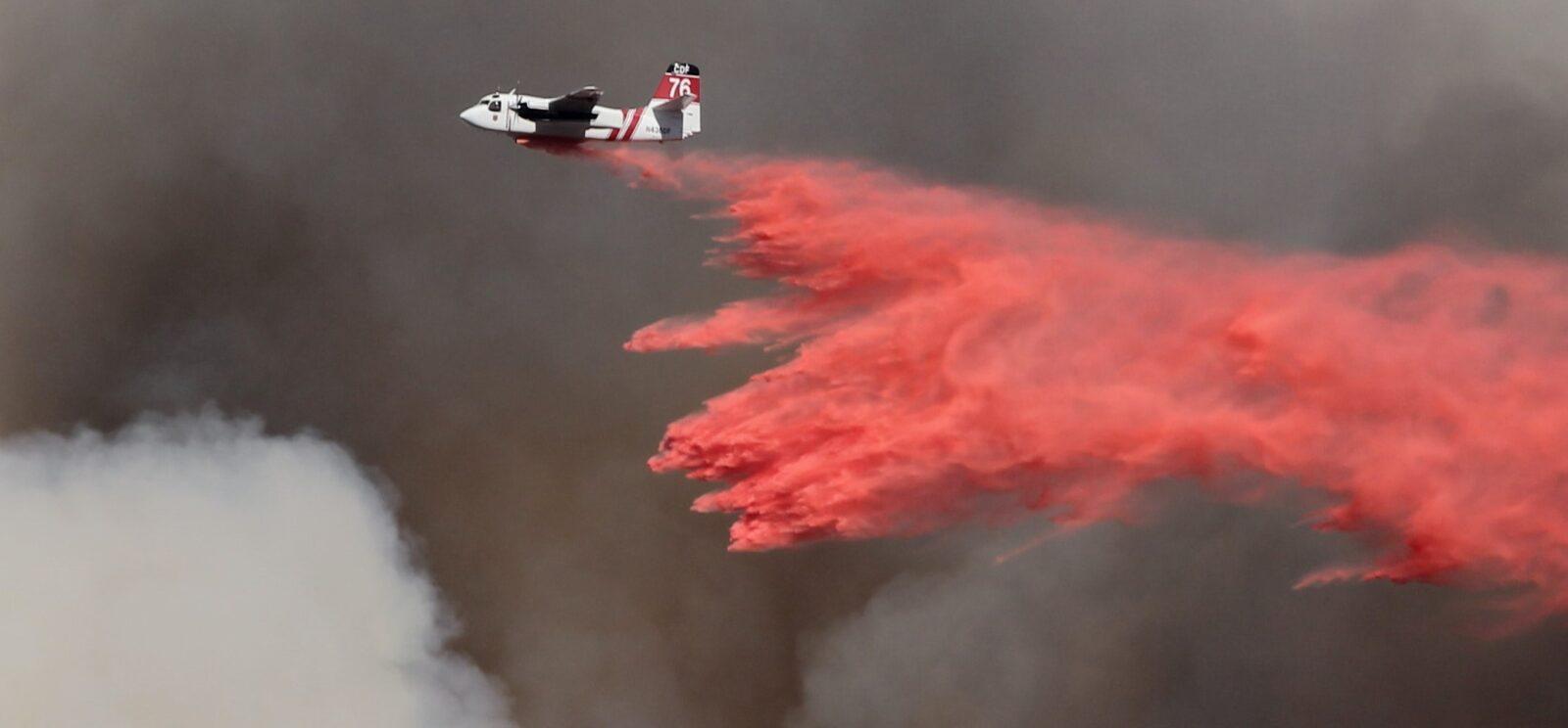 tanker drops fire retardant on wildfires amidst smoke cloud