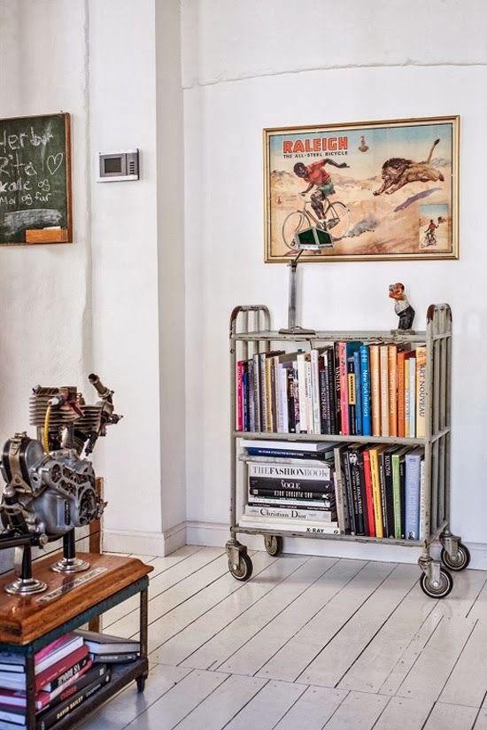 metal element Feng Shui   industrial wheeled book cart shelves picture frames white wood flooring   Girlfriend is Better
