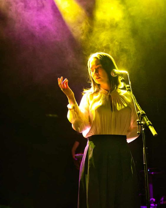 Mitski   Mitski on stage pink and yellow lighting   Girlfriend is Better