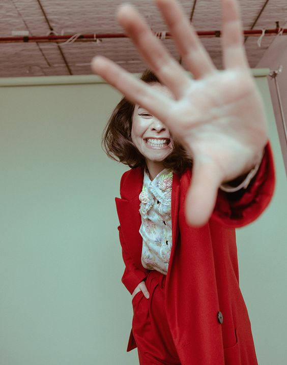 Mitski   Mitski red suit smiling and covering face   Girlfriend is Better