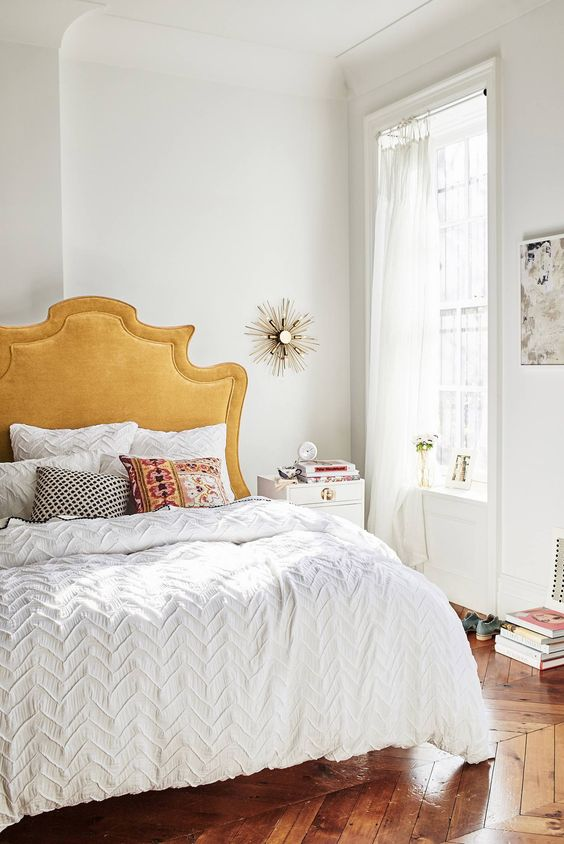 midsummer hygge bedroom decor   gold headboard white bedding sunburst mirror books   Girlfriend is Better
