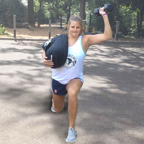 An image of a girl doing a lunge while holding a weighted dumbbell in one hand and holding a sandbag on her shoulder