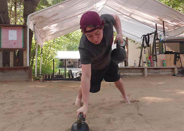 An image of a youth athlete training in a sand pit doing kettlebell rows