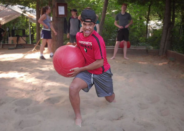 Athlete doing water ball walking lunges in a sand training pit