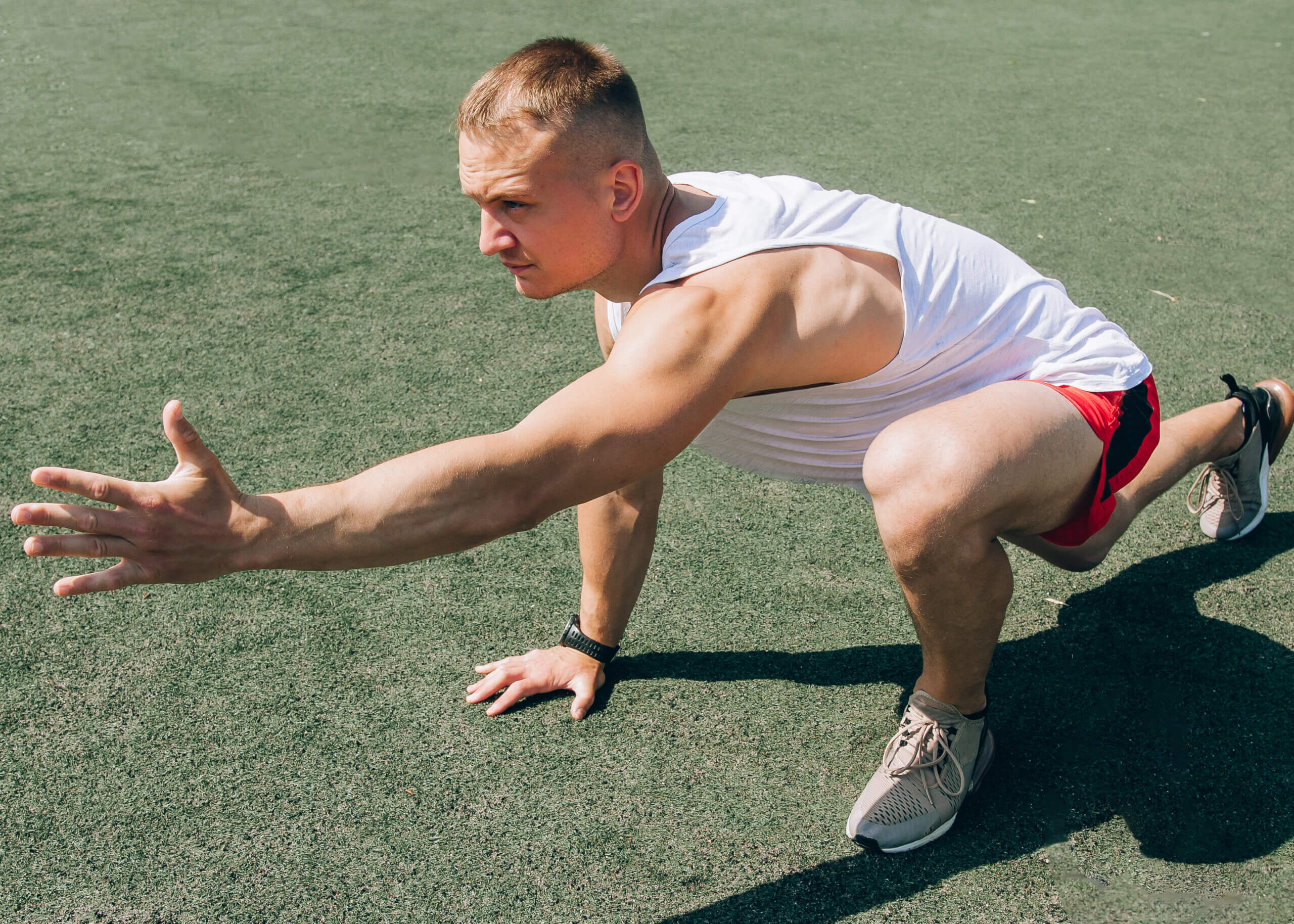 an image of a man doing sports yoga on a turf field
