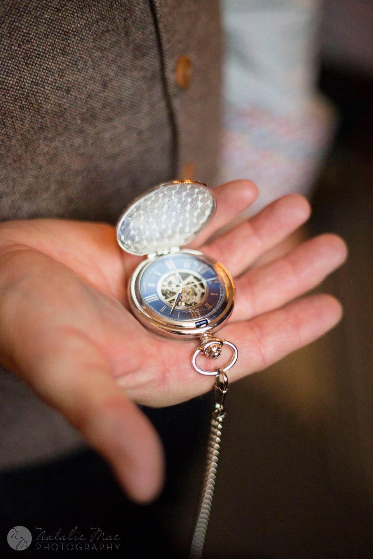 Groom holds compass similar to pocket watch - Michigan wedding photographer