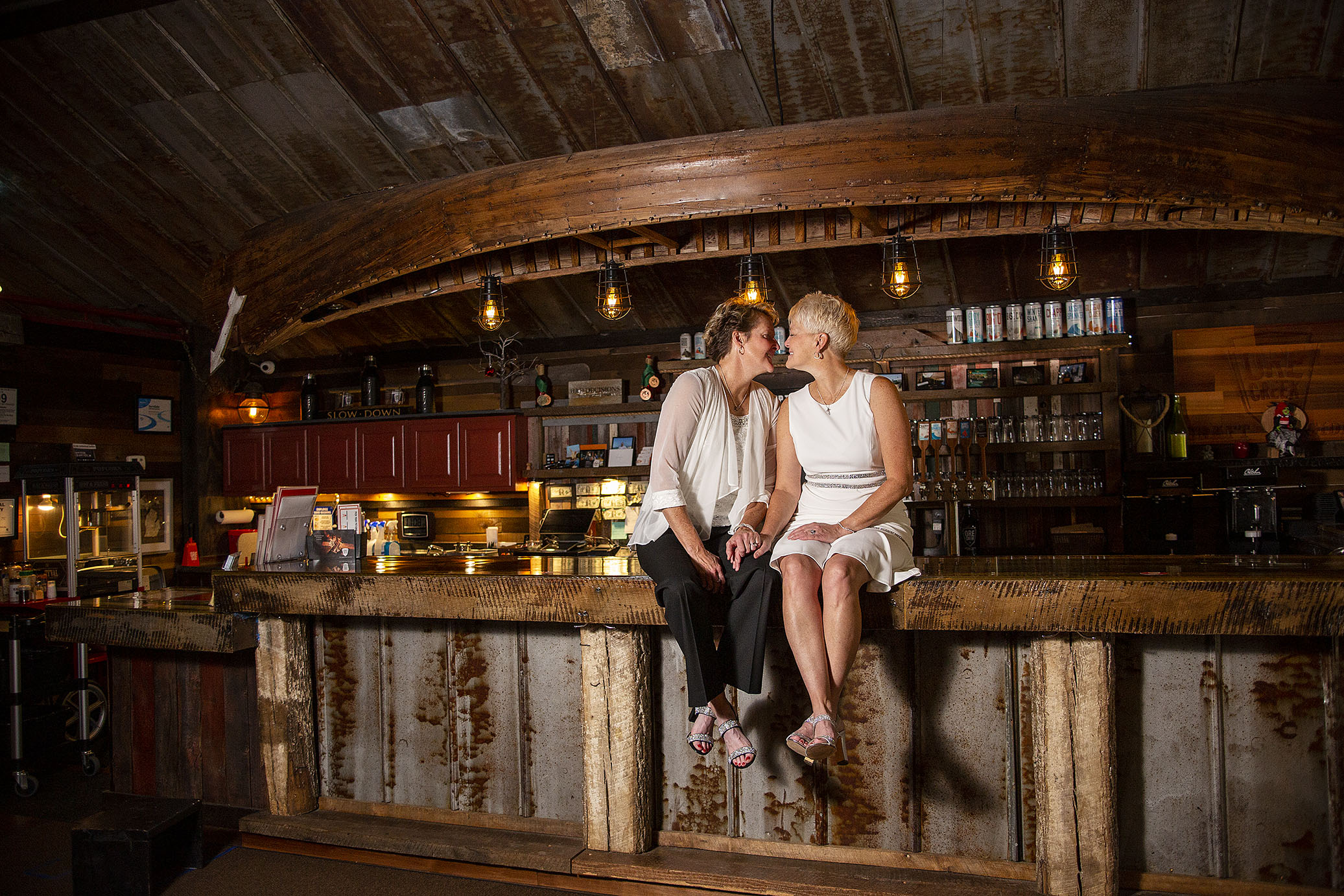 Lesbian couple kissing on top of the bar top at Ore Creek Cidery in Pinckney