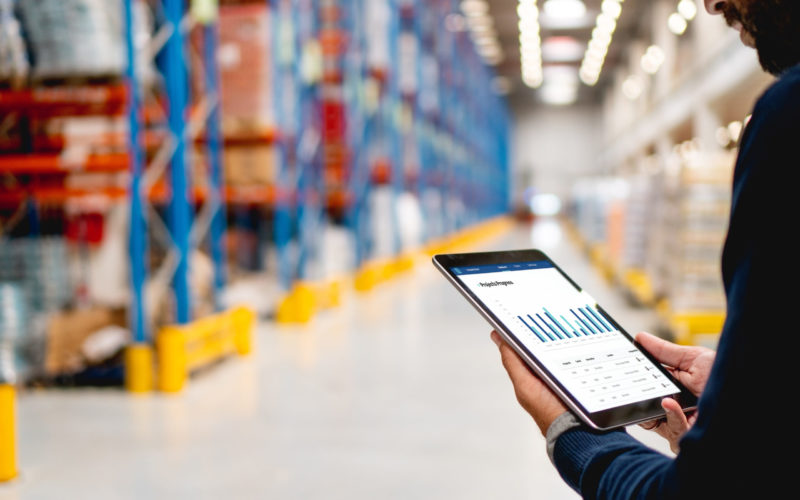 Manager in warehouse holding digital tablet