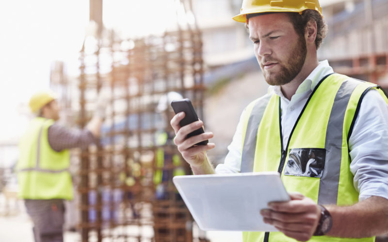 Construction worker digital tablet texting cell phone at construction site