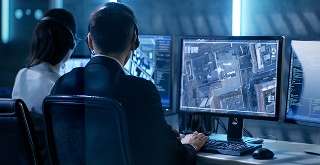 Government Agent is Tracking Fugitive with Her Computer in Big Monitoring Room Full of Computers with Animated Screens.
